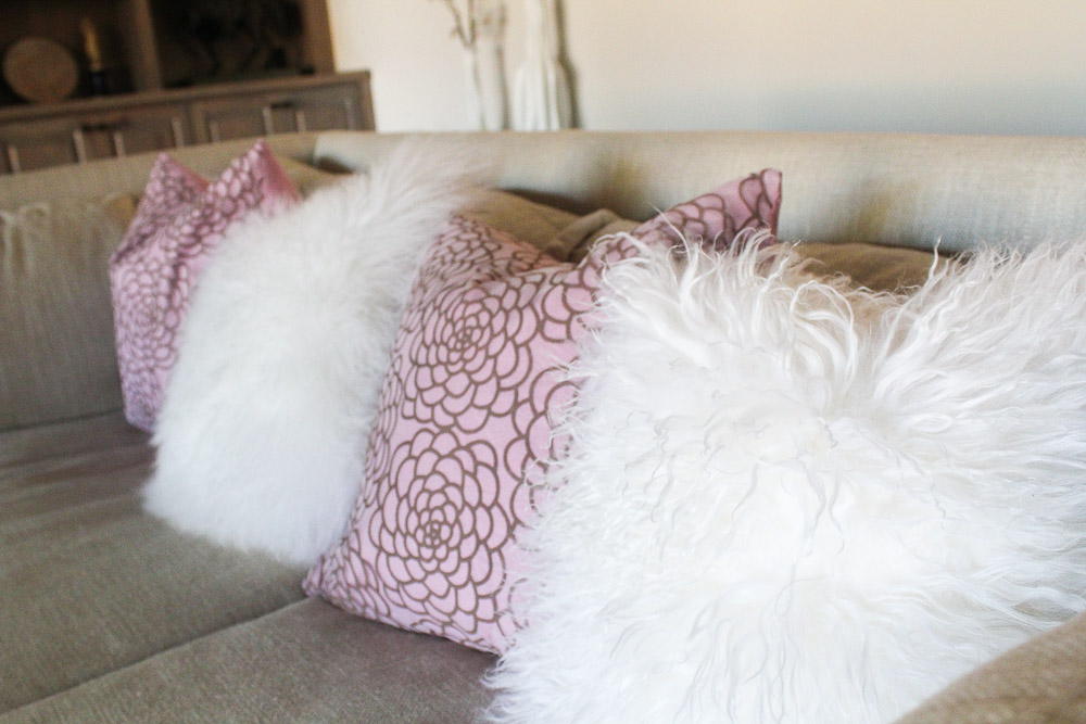 modern glam zen living room, white mongolian fur pillows and pink accents