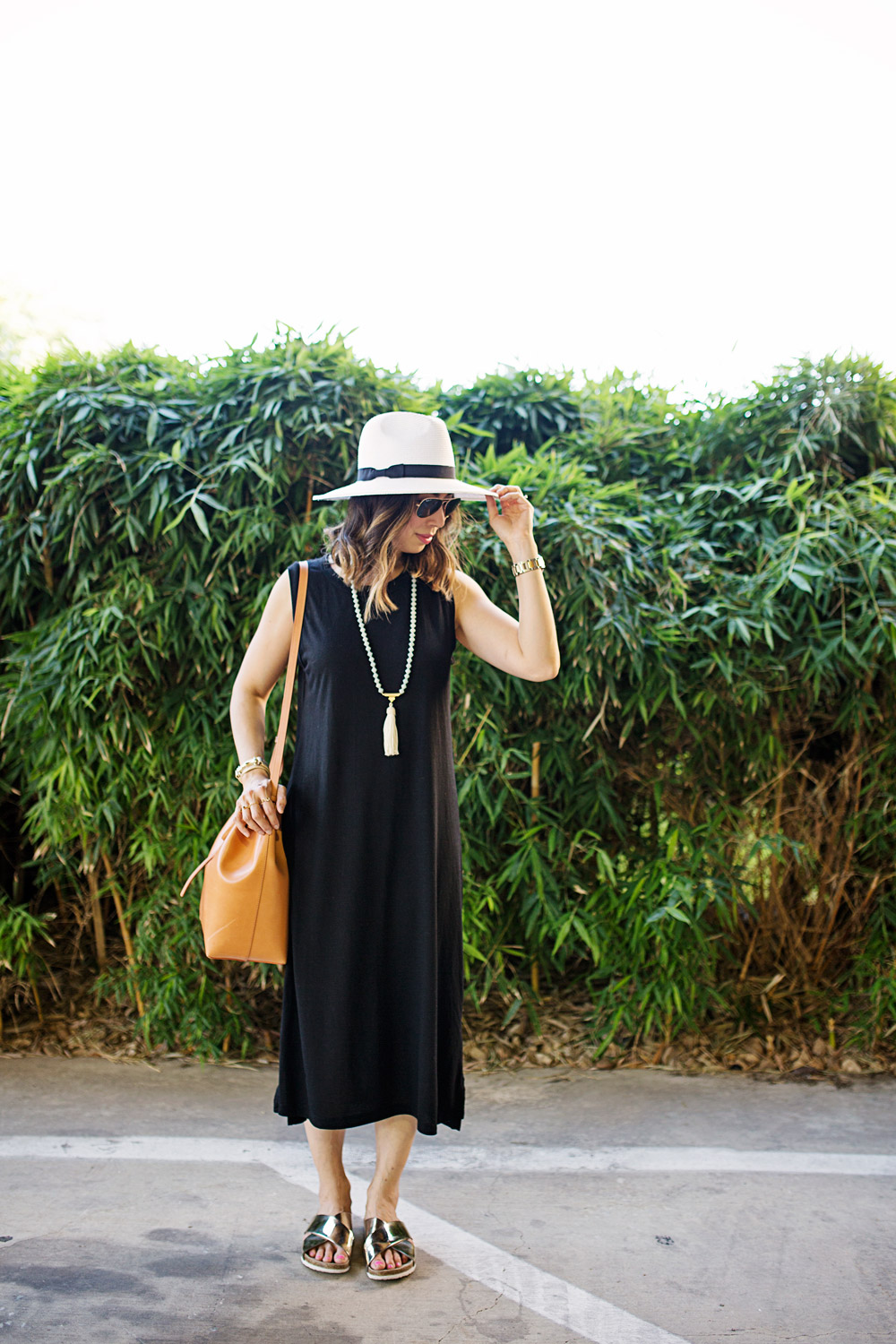 black sleeveless midi dress with panama hat and gold slides