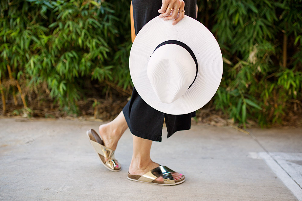 black midi dress and gold slides, panama hat