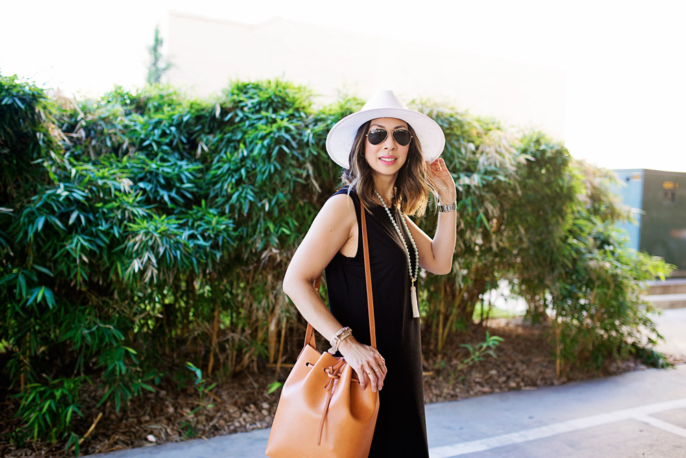 mommy blogger in black sleevless midi dress and mansur gavriel bucket bag