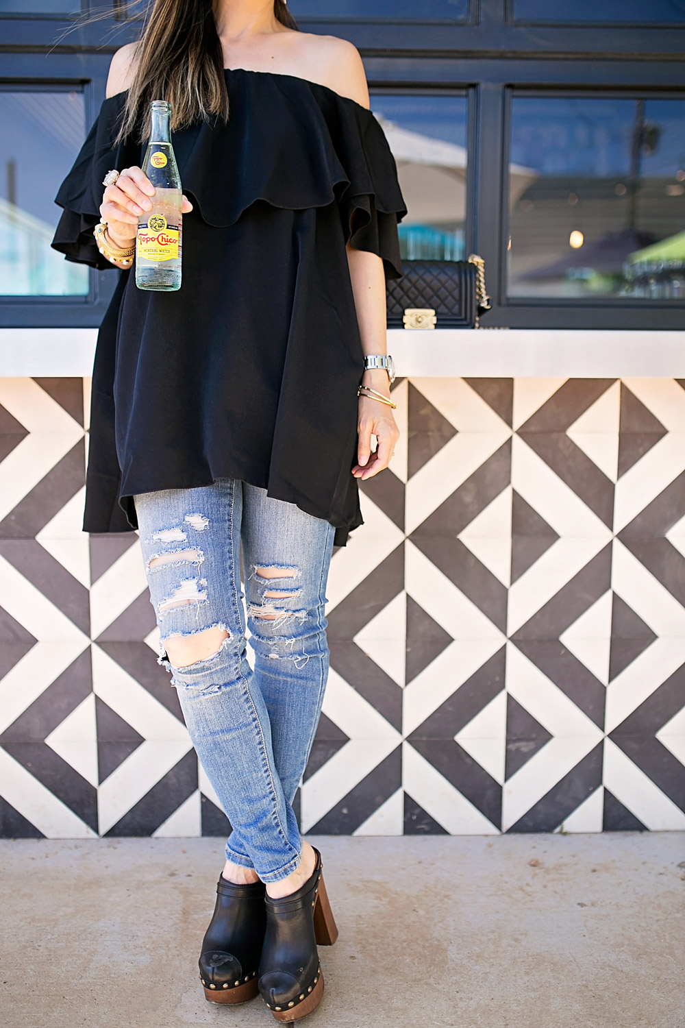 black off the shoulder dress with ripped jeans and clogs
