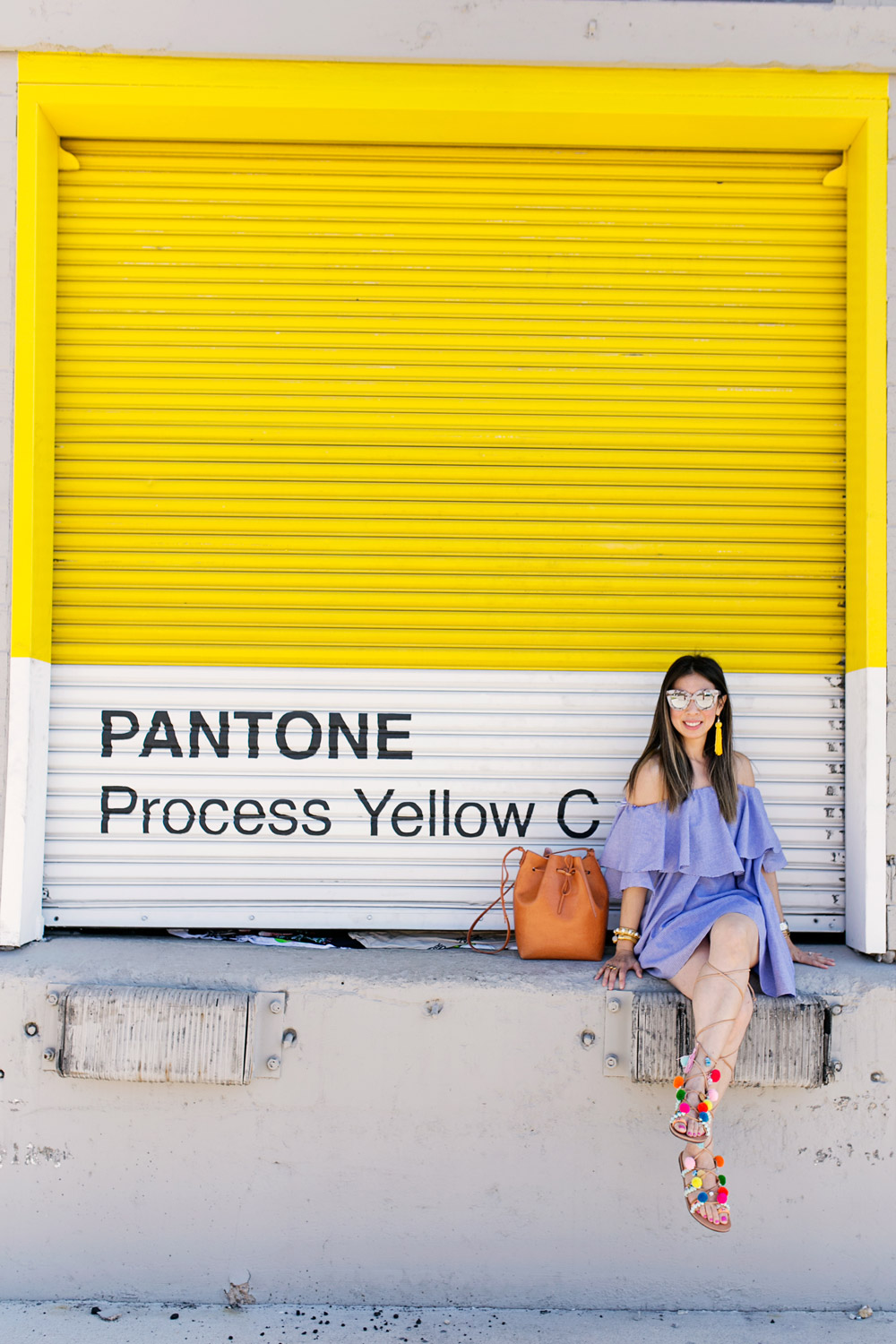 off the shoulder dress with pom pom sandals in front of yellow wall