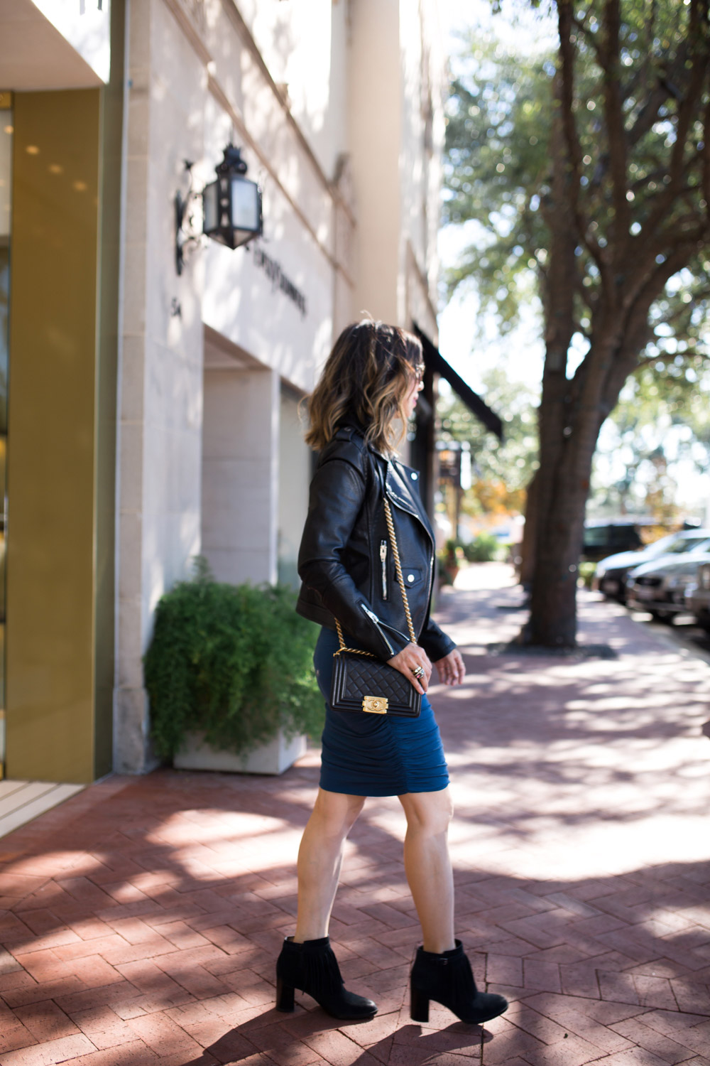 black moto jacket and fringe boots with blue ruched turtleneck dress