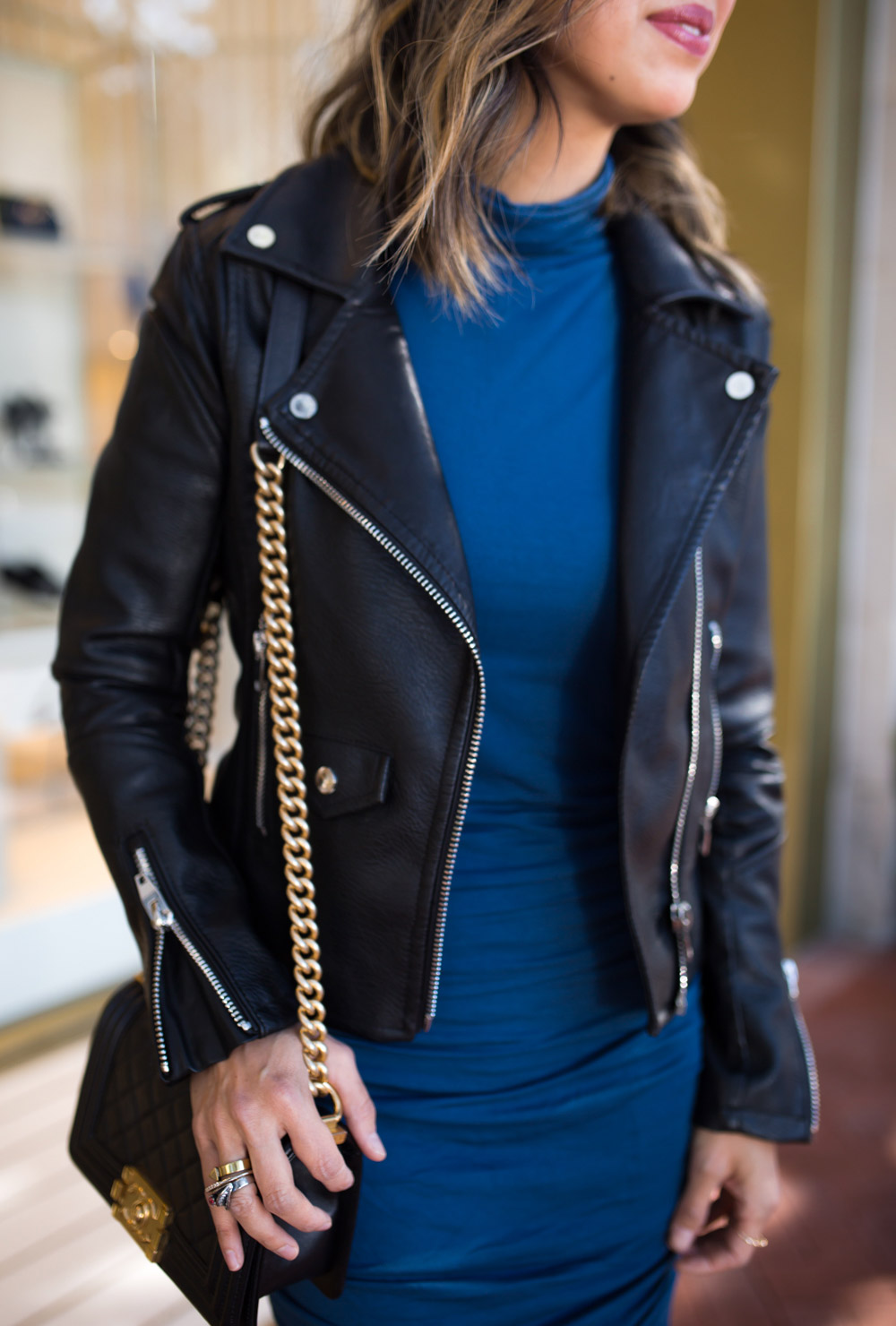black moto jacket with blue ruched turtleneck dress