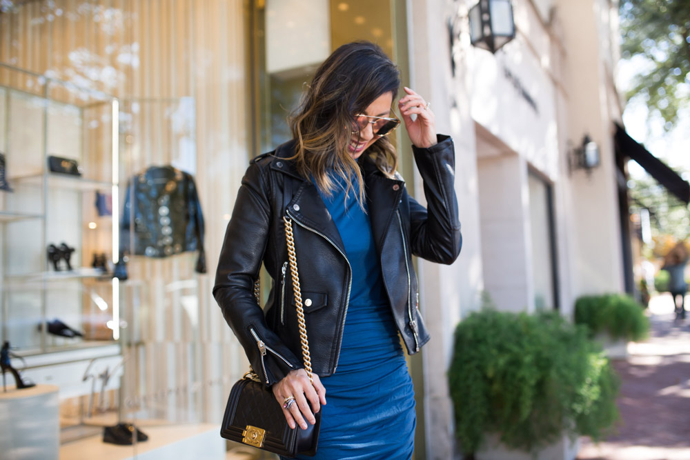 black moto jacket with blue ruched turtleneck dress and chanel boy bag