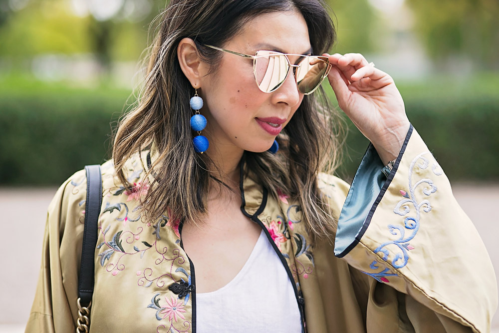rose gold reflective sunglasses, blue circle drop earrings, gold embroidered asian robe with white tank and levi's mom jeans