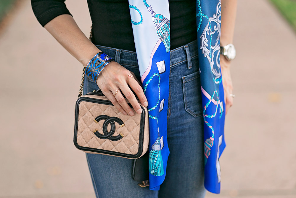 blue hermes maxi twilly with black top, flare jeans, and chanel filigree vanity bag