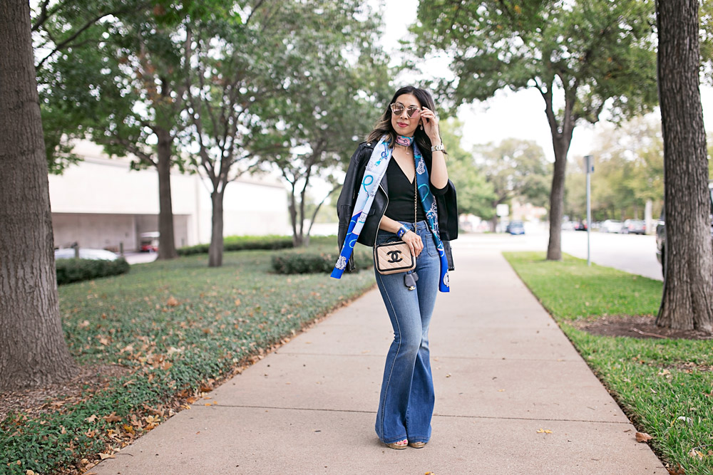 blue hermes maxi twilly with black top, flare jeans, and moto jacket