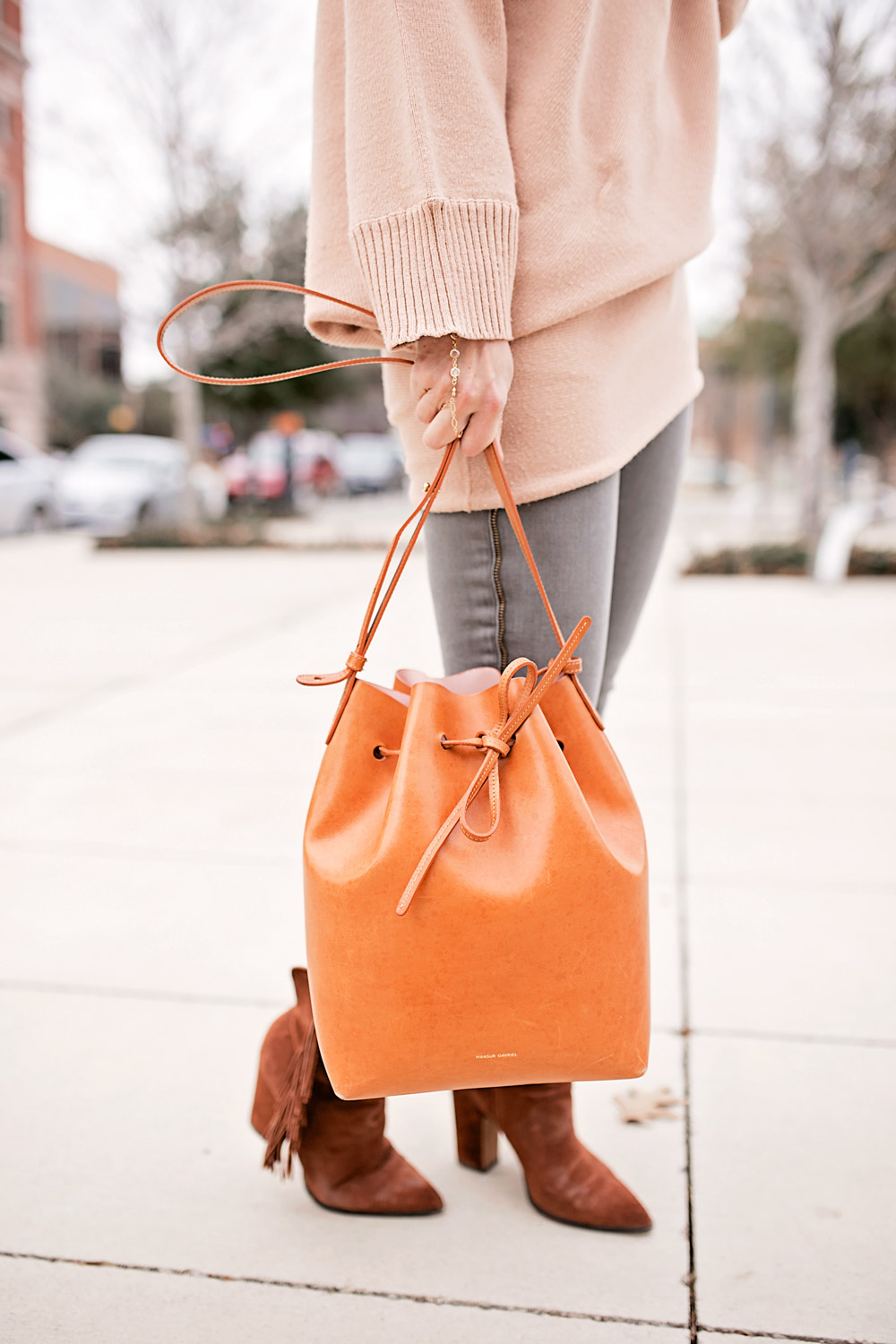 tan off the shoulder sweater with frame le skinny grey jeans, mansur gavriel bucket bag