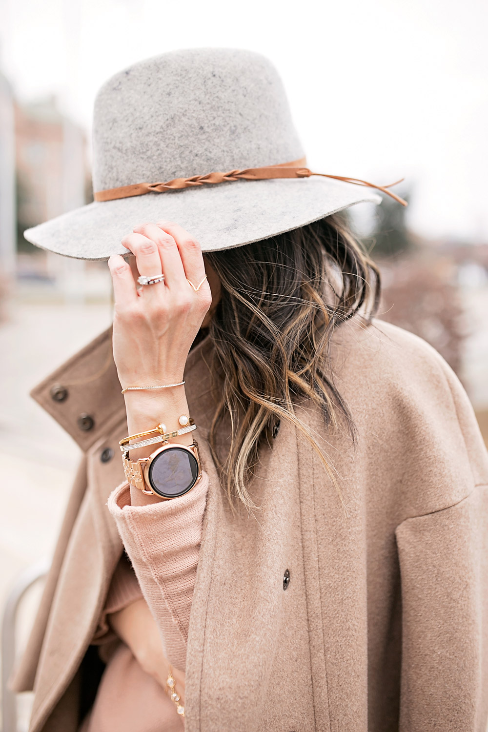 fossil q wander rose gold smartwatch, tan off the shoulder sweater with max mara coat,grey fedora