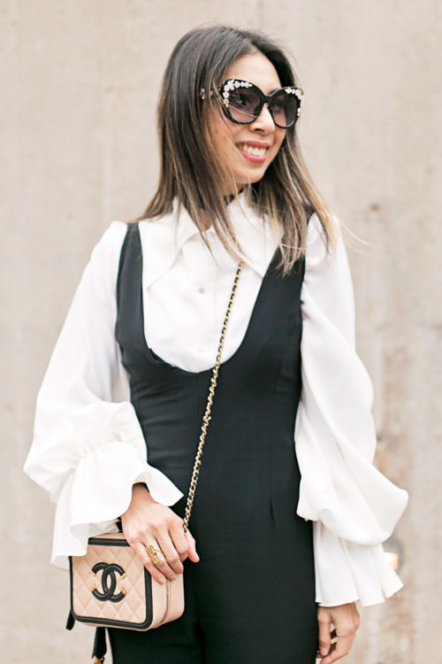 black jumpsuit with statement sleeve blouse and chanel vanity bag black and cream