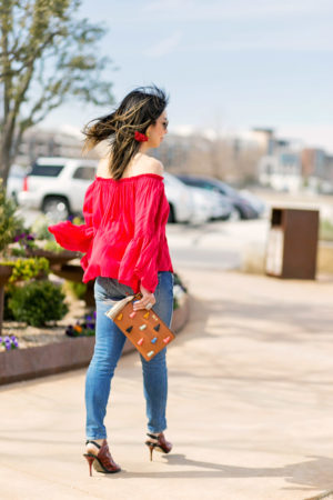 fossil tassel pouch, red off the shoulder top, amo twist jeans, balenciaga red glove sandals, galentines day outfit