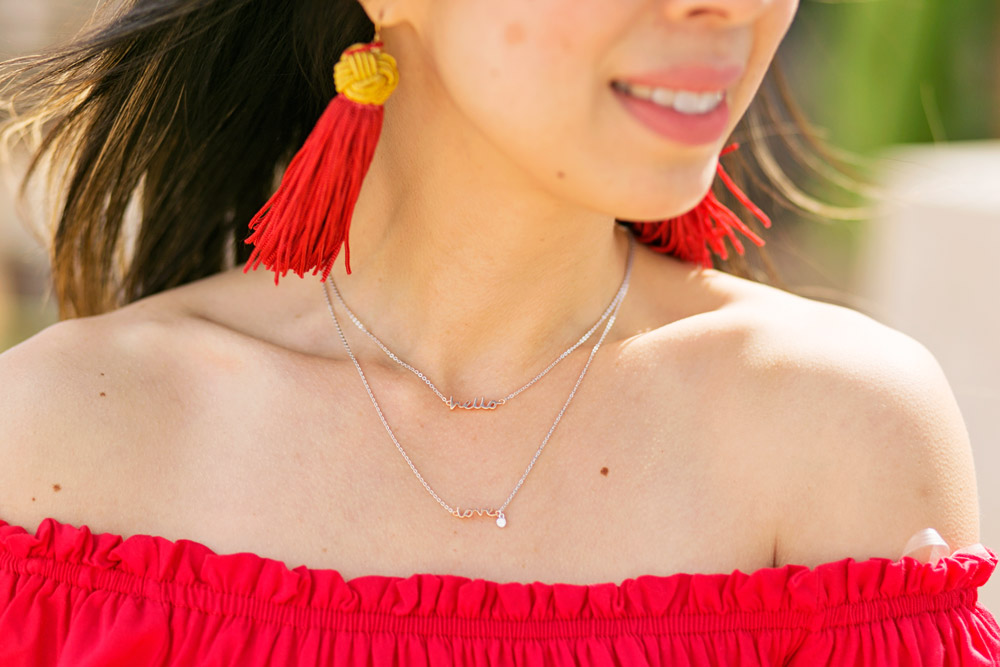 vanessa mooney red tassel earrings, off the shoulder top, fossil hello love necklace