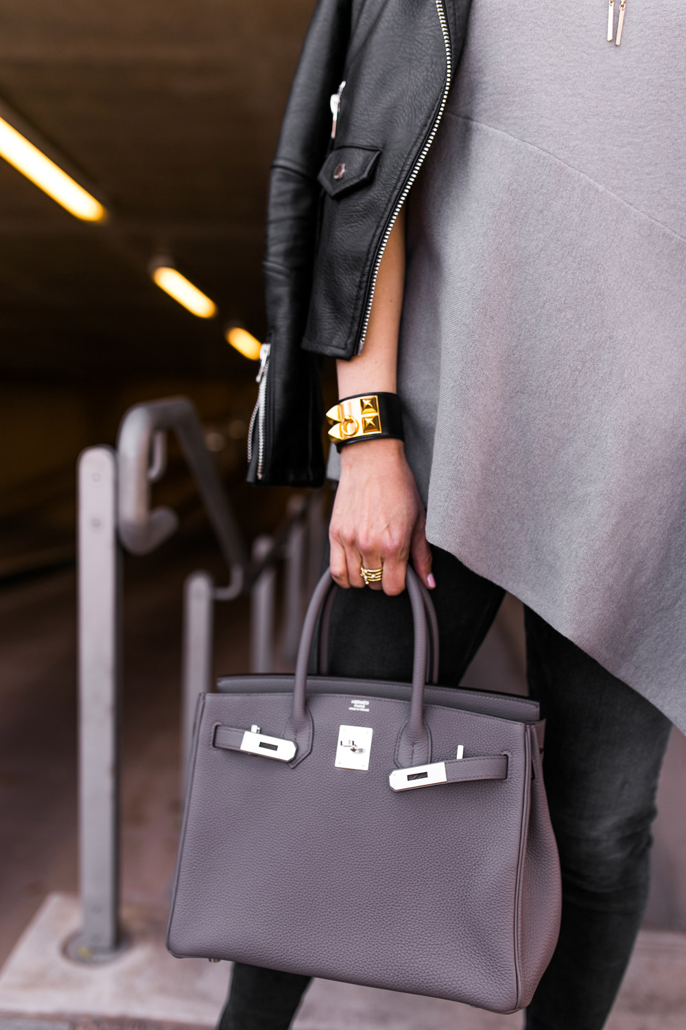 grey and black outfit, brochu walker asymmetrical hem top with hermes birkin 30 etaine and black blanknyc moto jacket and hermes cdc black and gold bracelet