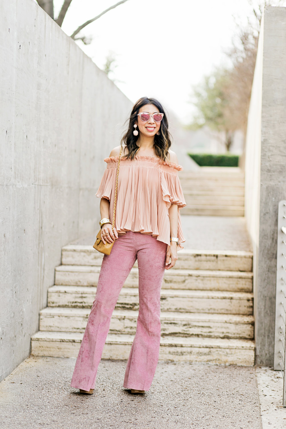 baublebar bahama pink pom pm earrings with endless rose pink pleated off the shoulder top and pink flare corduroy pants, chanel caviar mini flap, dior diorama pink mirrored sunglasses, spring outfit idea