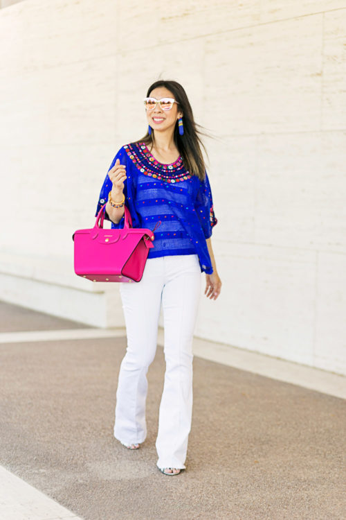 blue flower huipil with lele sadoughi tahitian nights striped fringe earrings and slider, nydj white farrah jeans, and pink longchamp bag