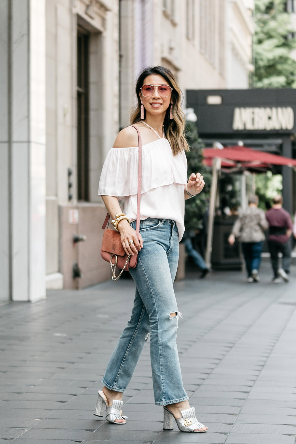 ruffle halter off the shoulder top with levi's 517 cropped flares and gucci silver marmont slides, rose pink chloe faye, bauble bar pinata tassel earrings, sonix rose pink aviator sunglasses