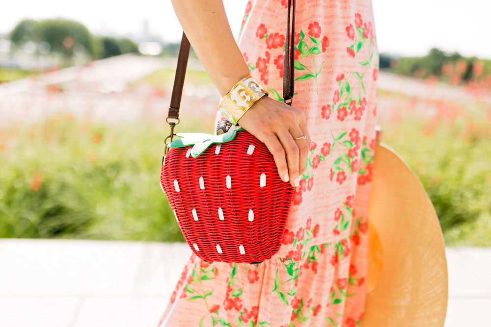 pink floral tiered maxi dress strawberry wicker bag cuyana oversized beach hat cherry earrings