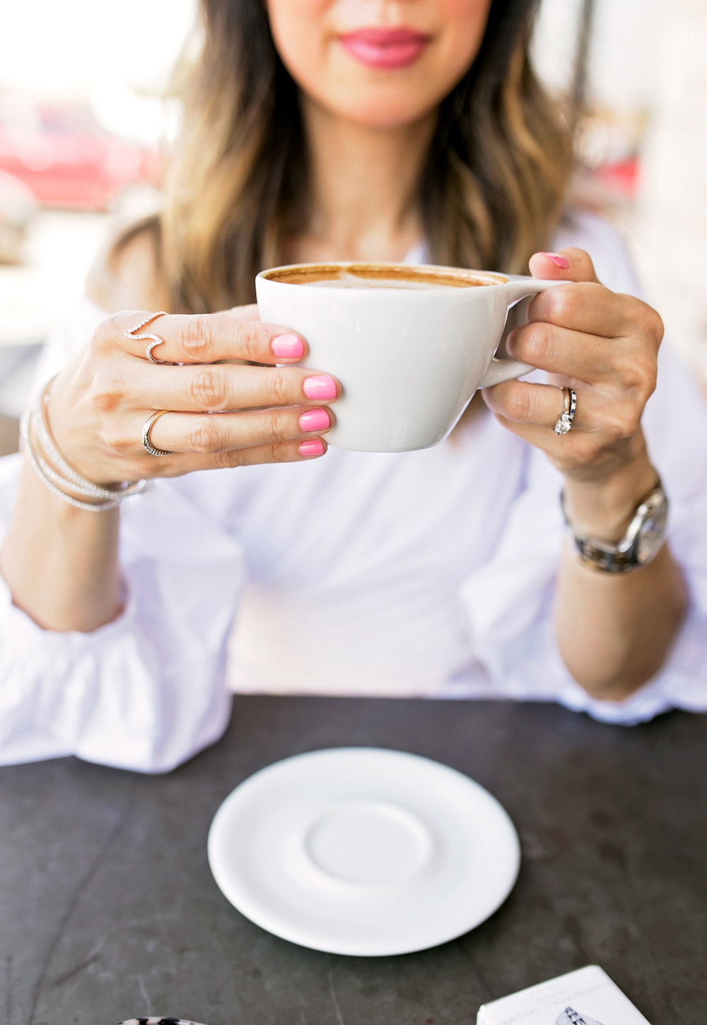 chic lady drinking cappuccino with pink nails diamond jewelry