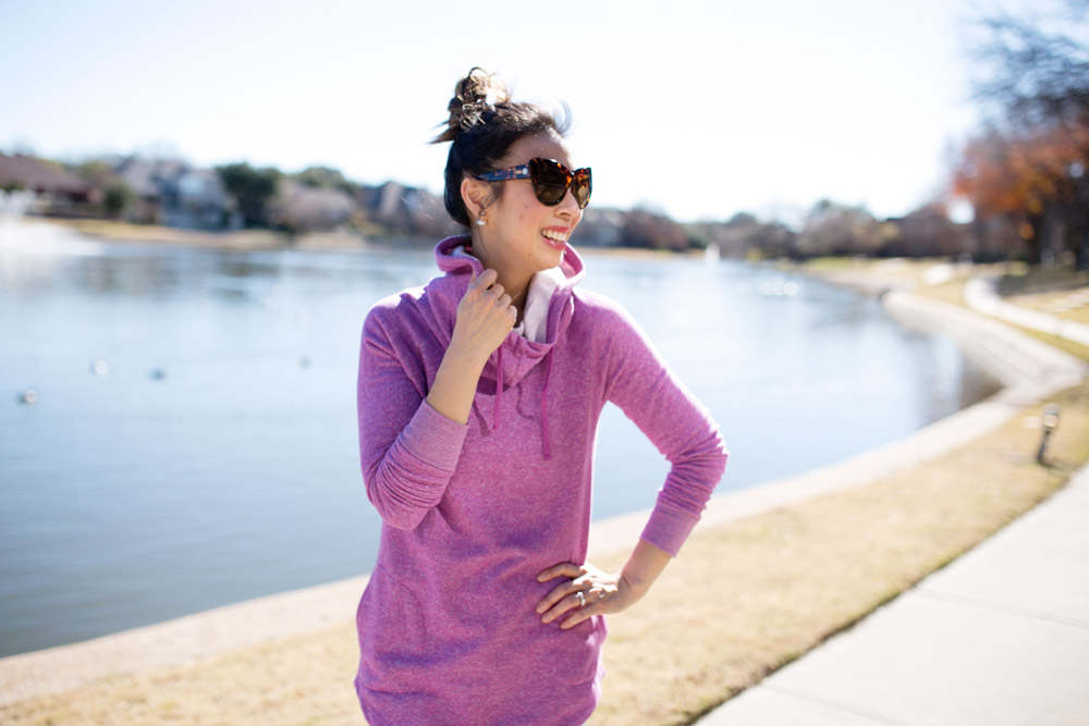 blogger exercising by lake with purple hoodie sunglasses